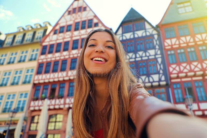 De mooie glimlachende vrouw neemt zelfportret in Romerberg-vierkant in Frankfurt, Duitsland royalty-vrije stock afbeeldingen