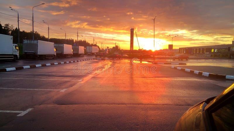 De mooie gouden oranje zonsondergang over industrieel het winkelen gebied van een Zelenograd-stad overdacht een asfaltvierkant, M stock fotografie