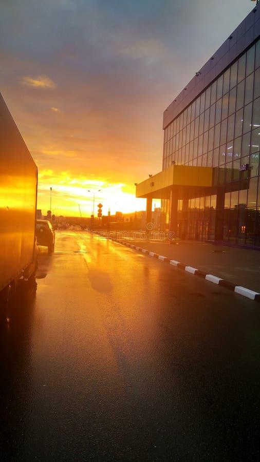 De mooie gouden oranje zonsondergang over industrieel het winkelen gebied van een Zelenograd-stad overdacht een asfaltvierkant, M stock foto's
