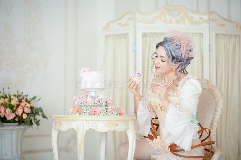 De mooie greyheadvrouw in Rococo's kleedt het stellen voor historische achtergrond terwijl het eten van cake stock afbeeldingen