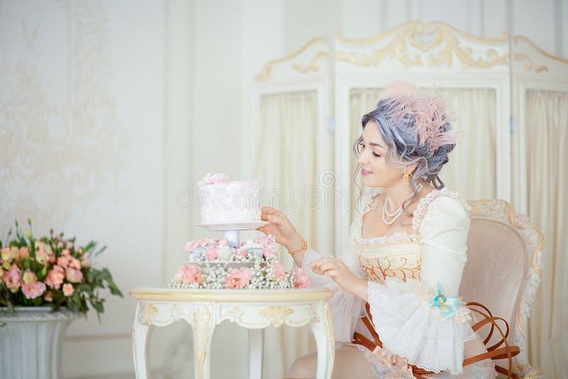 De mooie greyheadvrouw in Rococo's kleedt het stellen voor historische achtergrond terwijl het verfraaien van een cake stock afbeelding