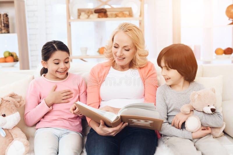 De mooie grootmoeder bekijkt fotoalbum met blije kleindochter en kleinzoonholdingsteddybeer royalty-vrije stock foto