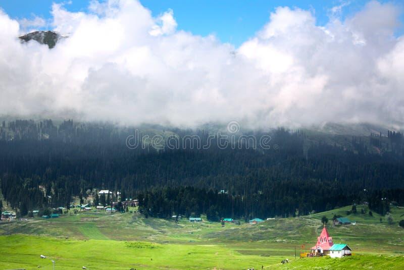 De mooie Grote bergmening, Groen gras, Weinig huis, Heel wat wit betrekt royalty-vrije stock afbeelding