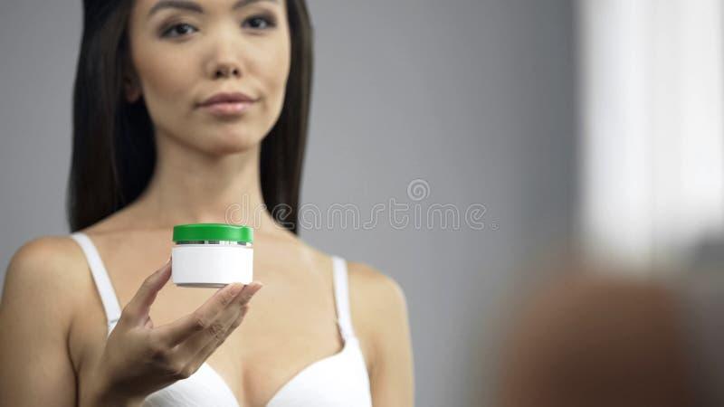 De mooie in hand kruik van de het gezichtsroom van de vrouwenholding, zich bevindt voor spiegel stock foto