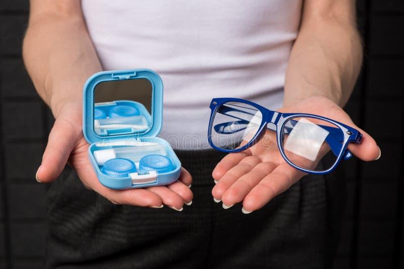 De mooie handen houden zachte contactlenzen en een container voor hen, en glazen royalty-vrije stock foto