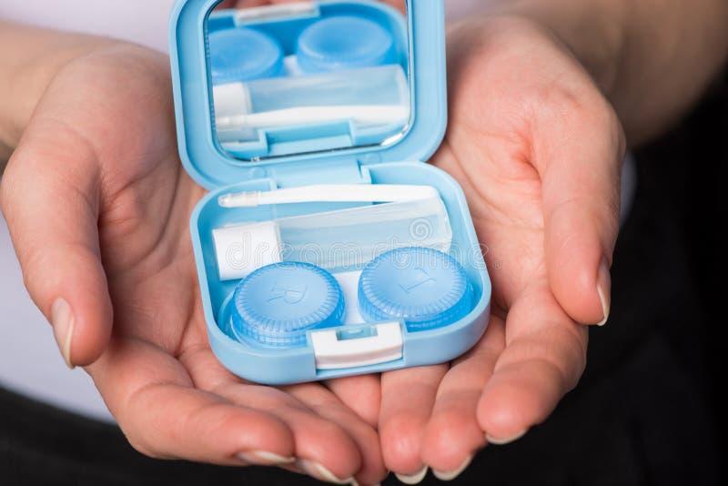 De mooie handen houden zachte contactlenzen en een container voor hen stock afbeeldingen