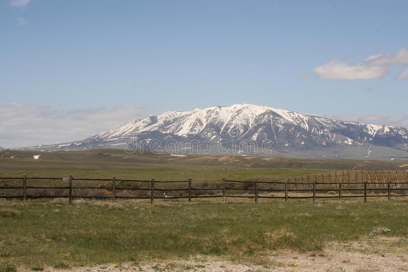 De mooie heldere dag met sneeuw behandelde bergen en groene grasrijke fileds met een een piketomheining en landbouwgrond royalty-vrije stock fotografie