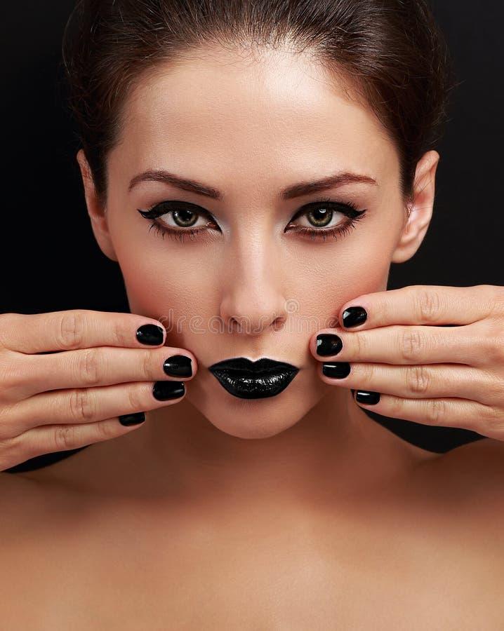De mooie heldere vrouw van de avondmake-up, zwart spijkerspoetsmiddel en zwarte lippenstift stock foto