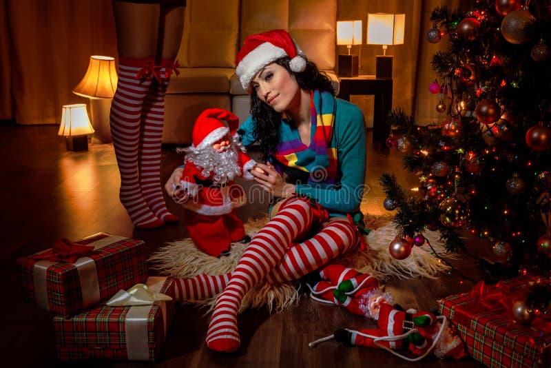 De mooie helper van vrouwensanta - naast Kerstmisboom stock fotografie