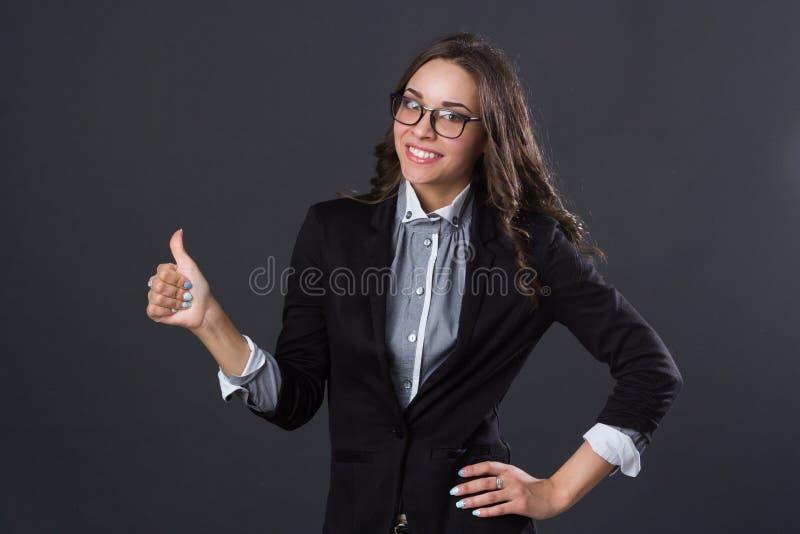De mooie het glimlachen duim van de meisjesholding omhoog stock foto