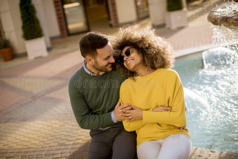 De mooie het glimlachen zitting van het liefdepaar dichtbij fontein op een zonnige dag stock foto