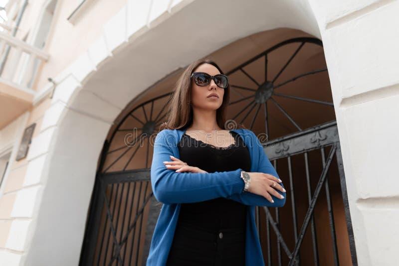 De mooie mooie hipster jonge vrouw in in kleren in modieuze zonnebril stelt op de straat dichtbij de uitstekende ijzerpoort stock fotografie