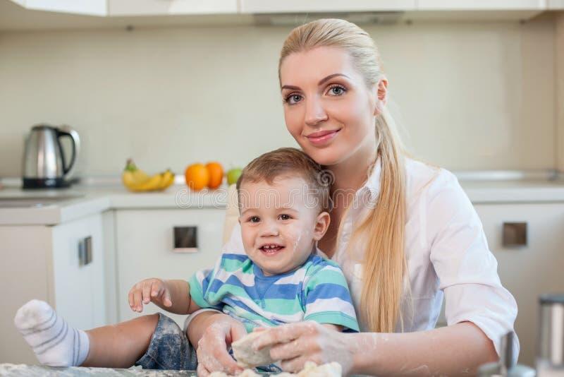 De mooie huisvrouw kookt met haar binnen jong geitje royalty-vrije stock afbeelding