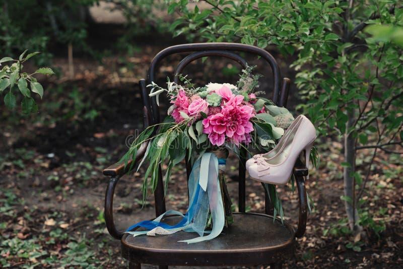 De mooie huwelijksschoenen met hoge hielen en een boeket van kleurrijke bloemen op een wijnoogst zitten op de aard voor royalty-vrije stock afbeelding