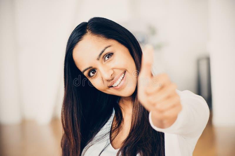 De mooie Indische vrouw beduimelt omhoog het gelukkige glimlachen stock fotografie