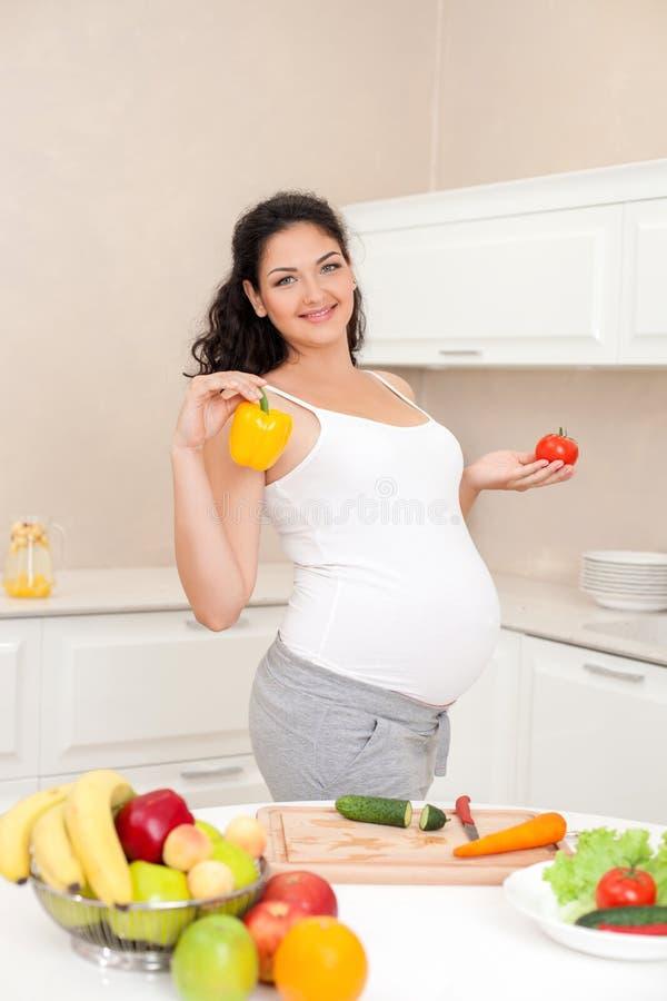 De mooie jonge aanstaande moeder kookt binnen royalty-vrije stock afbeelding