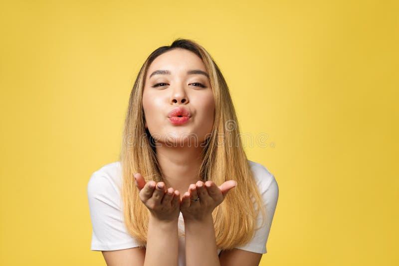De mooie jonge Aziatische die vrouw blaast een kus op gele achtergrond wordt geïsoleerd stock fotografie