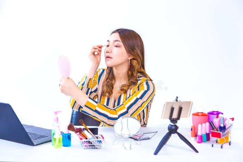 De mooie jonge Aziatische vloggervrouw die haar zetten maakt omhoog om online productoverzicht thuis te tonen stock afbeelding