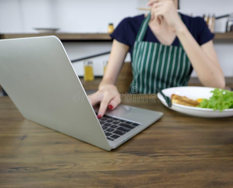 De mooie jonge Aziatische vrouw draagt schort eet ontbijt op een houten lijst in de eetkamer met laptop royalty-vrije stock afbeelding