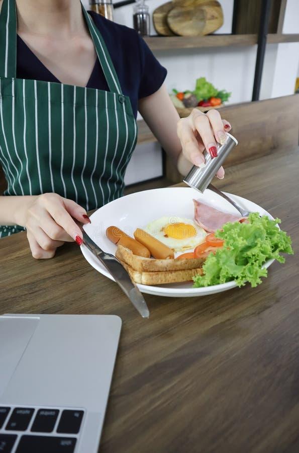 De mooie jonge Aziatische vrouw draagt schort eet ontbijt op een houten lijst in de eetkamer met laptop stock foto