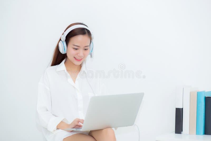De mooie jonge Aziatische vrouw ontspant met slijtagehoofdtelefoon geniet het luisteren van muziek gebruikend laptop computer royalty-vrije stock afbeelding