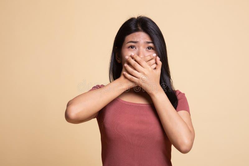 De mooie jonge Aziatische vrouw sluit haar mond stock afbeelding