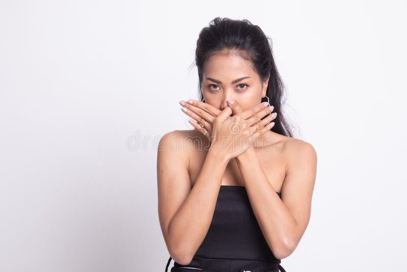 De mooie jonge Aziatische vrouw sluit haar mond stock foto's
