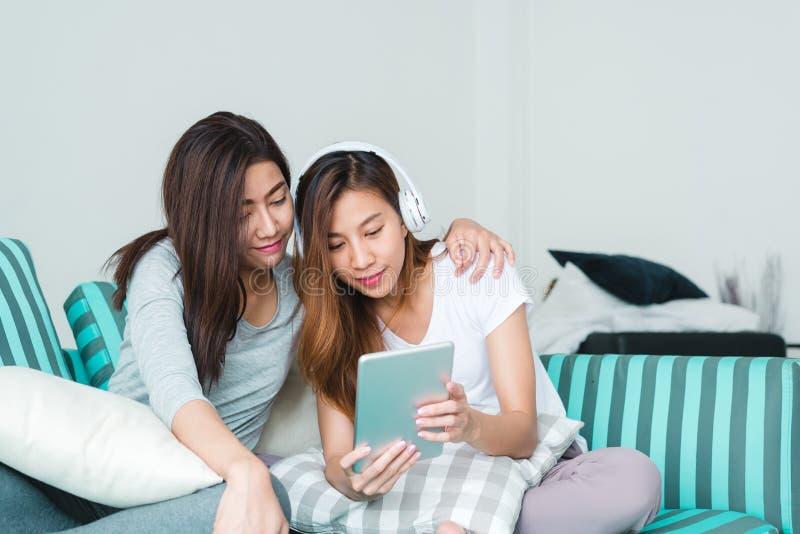 De mooie jonge Aziatische zitting van het vrouwenlgbt lesbische gelukkige paar op bank die online gebruikende tablet in woonkamer stock fotografie