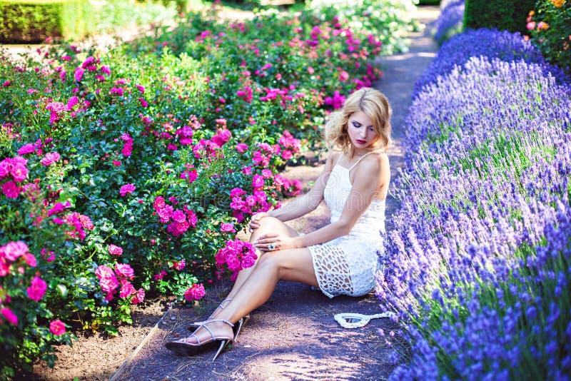 De mooie jonge bloeiende lavendel en de rozen van de meisjeszitting dichtbij royalty-vrije stock foto
