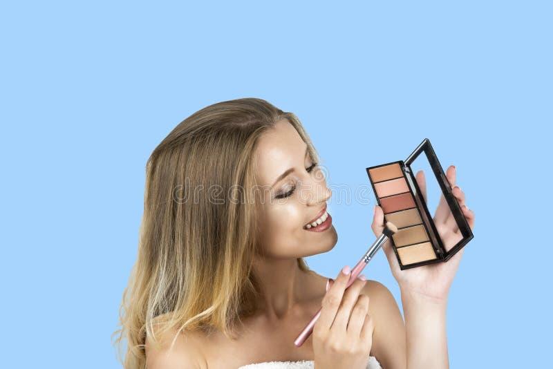 De mooie jonge blonde borstel van de vrouwenholding en eyeshagow palet geïsoleerde blauwe achtergrond royalty-vrije stock foto's