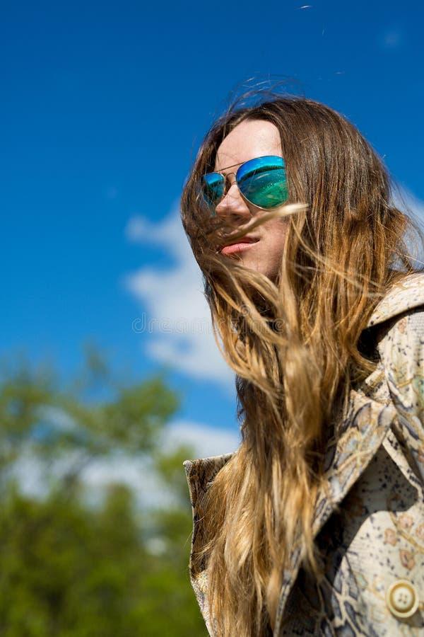 De mooie jonge blonde vrouw die in openlucht van de zon in de lente genieten, wordt een warme filter toegepast, de wind in uw haa stock foto's