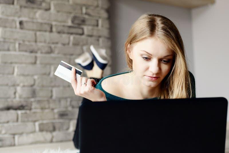 De mooie jonge blonde vrouw koopt op Internet stock foto's