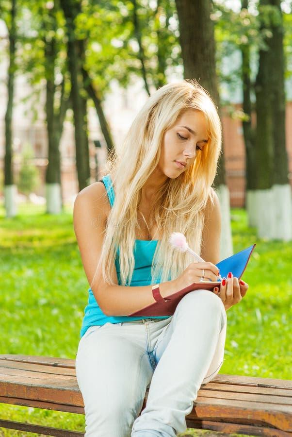 De mooie jonge blondevrouw in blauwe t-shirt zit op bank en w stock fotografie