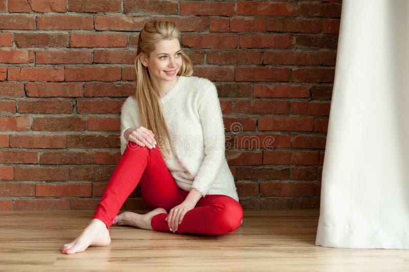 De mooie jonge blondevrouw in een wit warm jasje en rode zhdinsah, zitten op de vloer dichtbij het venster, tegen een rode bakste stock foto's