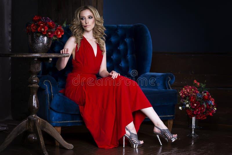 De mooie jonge blondevrouw in rode kleding met Halloween maakt omhooggaand en bloedig gezichtsart. stock fotografie