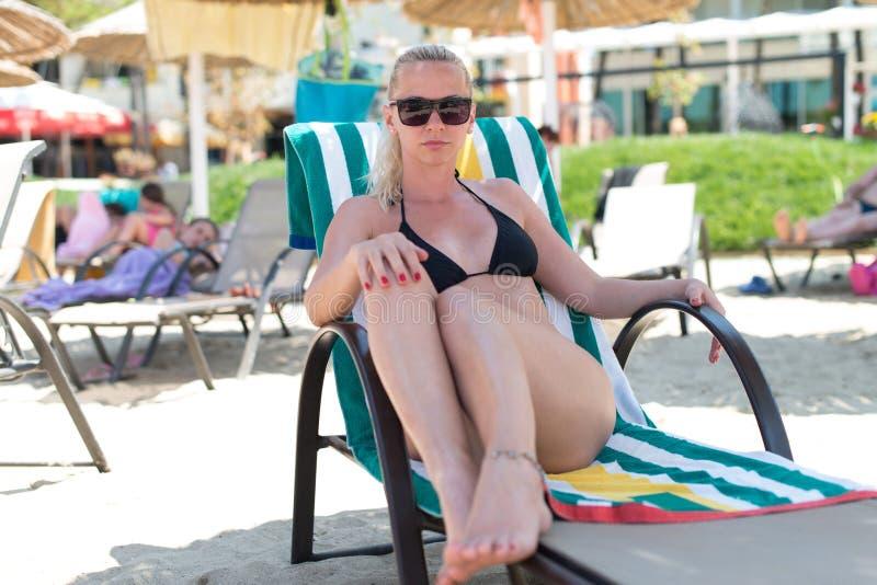 De mooie Jonge Blondevrouw zonnebaadt op het Strand stock afbeeldingen