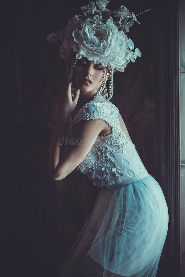 De mooie jonge bruid die witte kleding en kroon van bloemen dragen zit op een stoel Luxepaleis stock afbeeldingen