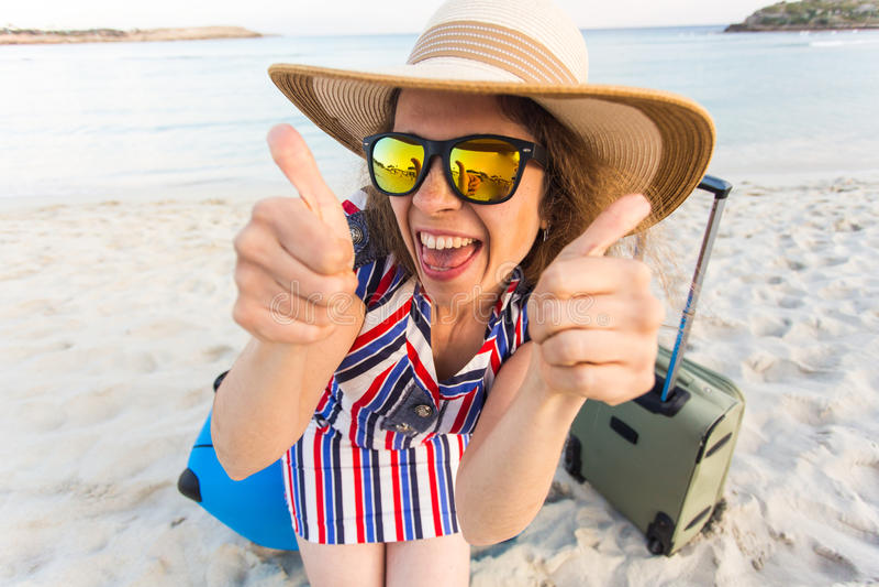 De mooie jonge dame met het blauwe koffer tonen beduimelt omhoog gebaar op het strand Mensen, reis, vakantie en de zomer stock afbeelding