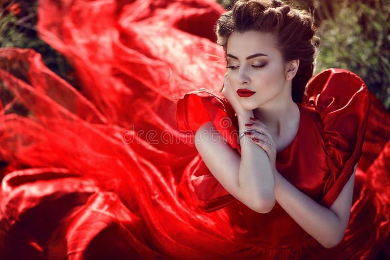 De mooie jonge dame met perfect maakt en vlechtte omhoog kapsel die luxueuze zijde dragen rode kledingszitting op het papavergebi stock fotografie