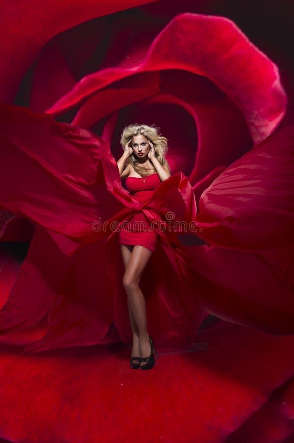De mooie jonge dame in rode kledingstribunes op bloem nam toe royalty-vrije stock foto's