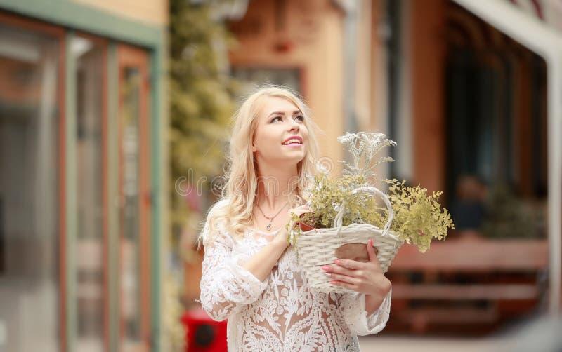De mooie jonge dame in de zomerhoed die in openluchtkoffie rusten propped gezicht met hand en wachtende vriend Openluchtportret v royalty-vrije stock foto's