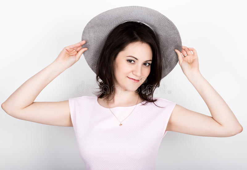 De mooie jonge donkerbruine vrouw die a houden breed-brimmed hoed, zij uitdrukking van verschillende emoties stock afbeelding