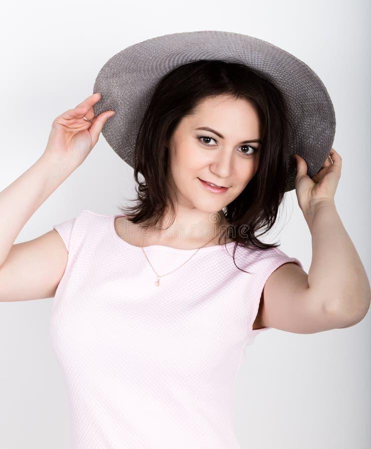 De mooie jonge donkerbruine vrouw die a houden breed-brimmed hoed, zij uitdrukking van verschillende emoties stock afbeeldingen