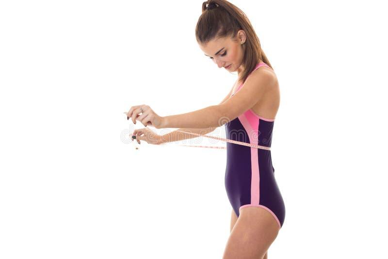 De mooie jonge donkerbruine vrouw in lichaamszwempak meet haar die taille met band op witte achtergrond wordt geïsoleerd stock afbeelding