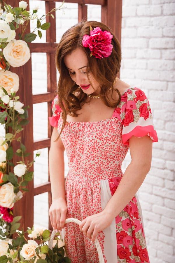 De mooie jonge donkerbruine vrouw met bloem in haar houdt bascket hoogtepunt van bloemen stock foto's