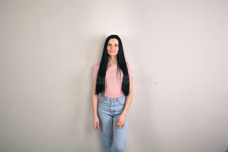 De mooie jonge donkerbruine vrouw met lang haar bevindt zich door de grijze achtergrond kijkend recht aan de camera wearing stock afbeelding