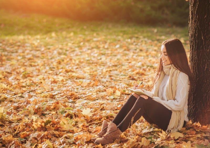De mooie jonge donkerbruine zitting op de gevallen herfst gaat in een park, lezing een weg boek of schrijft een agenda stock afbeeldingen