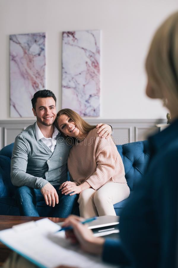 De mooie jonge echtgenoot en de vrouw bezoeken een psycholoog Sitting en het omhelzen stock fotografie