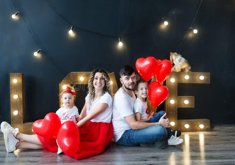 De mooie jonge familie en hun kleine jonge geitjes stellen met ballons in een comfortabele studio Het portret van de studiofamili royalty-vrije stock foto's
