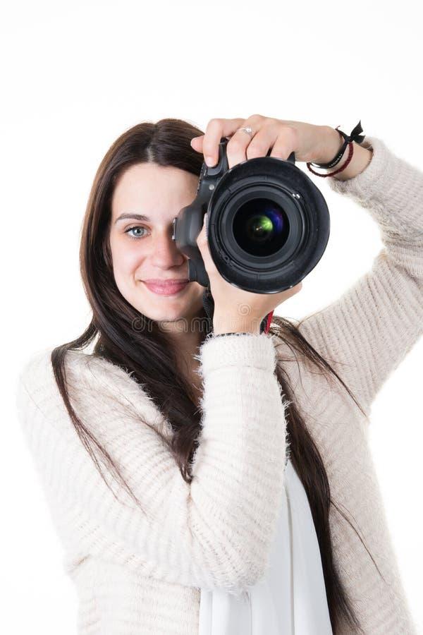 De mooie jonge fotograaf die van de vrouwentrainer beelden op witte achtergrond nemen royalty-vrije stock afbeelding
